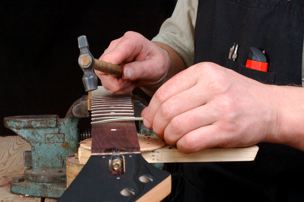 Luthier working on acoustic guitar